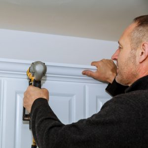 Handyman using brad nail gun on installation crown moulding wall kitchen cabinets trim